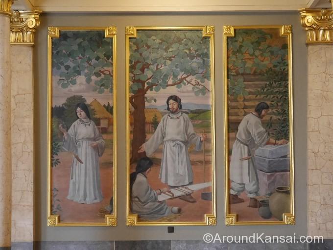 フトダマノミコト(中央)、足元には機を織る女性、左には鏡を持つ女性、右には勾玉をみがく男性が描かれています